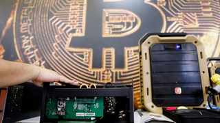 Image: A cryptocurrency mining computer is seen in front of bitcoin logo during the annual Computex computer exhibition in Taipei