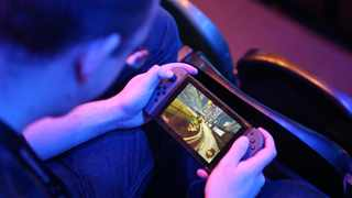 A fan plays Rocket League on a Nintendo Switch during day one of the Rocket League Championship Series Finals in London. Photo: Reuters.