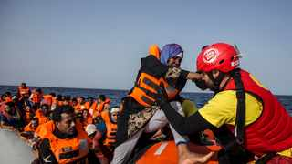 A migrant aboard a rubber dinghy off the Libyan coast is helped by rescuers aboard the Open Arms aid boat, of Proactiva Open Arms Spanish NGO. File picture: Olmo Calvo/AP