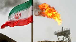 An Iranian flag is seen in front of a gas flare on an oil production platform in the Soroush oil fields in Iran. Picture: Reuters