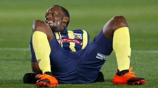 Usain Bolt lies on the pitch after taking a shot at goal during a friendly trial soccer match between the Central Coast Mariners and the Central Coast Select in Gosford, Australia. Photo: AP Photo/Steve Christo