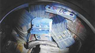 In this image released by the Amsterdam Police on Thursday Nov. 22, 2018, confiscated money is seen. Police in Amsterdam say they have detained a 24-year man on suspicion of money laundering after discovering 350,000 euros (dollars US 400,000) in cash hidden in a washing machine. Police said in a statement Thursday that officers were checking a house in western Amsterdam on Monday for unregistered residents when they found the valuable laundry load. (Dutch Police via AP)