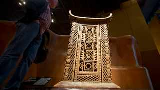 A visitor looks at the wooden and metal throne of the King Ghezo of the Dahomey kingdom, dated 19th century, today's Benin at Quai Branly museum in Paris, France. OFS announced a R221 457 600 initiative to support the restitution of looted African artefacts. File photo: AP Photo/Michel Euler.