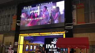"In this Tuesday, Dec. 4, 2018, photo, a worker stands underneath a screen advertising the movie ""Crazy Rich Asians"" at a cinema in Beijing. Chinese audiences aren't exactly going nuts over the U.S. box office hit ""Crazy Rich Asians,"" despite its all-Asian cast and theme of rising Asian prosperity. (AP Photo/Fu Ting)"