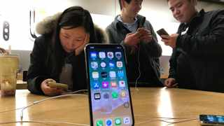 FILE - In this Nov. 6, 2017, file photo, shoppers check out the iPhone X at an Apple store in Beijing, China. U.S. chipmaker Qualcomm says it's won an order in a Chinese court banning some Apple phones in China as part of a long-running dispute over patents. Qualcomm said Monday, Dec. 10, 2018, that the Fuzhou Intermediate People's Court in China has granted preliminary injunctions ordering four Chinese subsidiaries of Apple to stop selling and importing iPhones 6S through X. (AP Photo/Ng Han Guan, File)