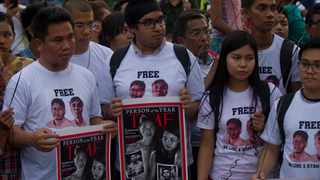 Activists holding signs with the Time Magazine cover with wives of two Reuters journalists stand during a rally to mark one year anniversary of their arrest, Wednesday, Dec. 12, 2018, in front of city hall in Yangon, Myanmar. On Dec 24, lawyers lodged an appeal to free the two journalists jailed for their reporting on Myanmar's Rohingya crisis.(AP Photo/Thein Zaw)