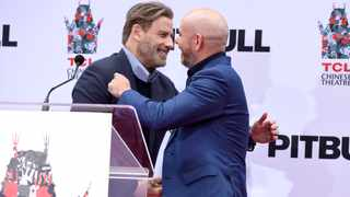 Actor John Travolta, left, greets rapper Pitbull during a hand and footprint ceremony in Pitbull's honor at the TCL Chinese Theatre on Friday, Dec. 14, 2018, in Los Angeles. (Photo by Chris Pizzello/Invision/AP)