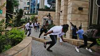 Civilians flee as security forces aim their weapons at the buildings of a hotel complex in Nairobi, Kenya. Picture: AP Photo/Khalil Senosi