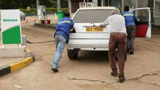 A motorist is helped to push his car into a garage after it ran out out of fuel, in the capital Harare,. (AP Photo/Tsvangirayi Mukwazhi)