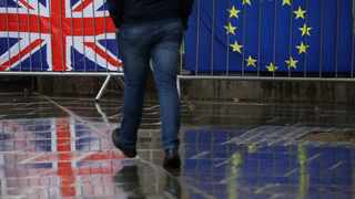 Flags tied to railings outside parliament are reflected on a wet pavement in London. Picture: Kirsty Wigglesworth/AP