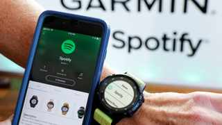 FILE- In this Oct. 3, 2018, file photo a Garmin International employee shows the new Spotify app on his smartphone integrated with his Garmin fenix 5 Plus watch during a presentation in New York. Spotify reports financial results Wednesday, Feb. 6, 2019. (AP Photo/Richard Drew, File)