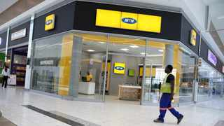 FILE PHOTO: A worker walks past an outlet of South Africa's MTN Group in Johannesburg, South Africa