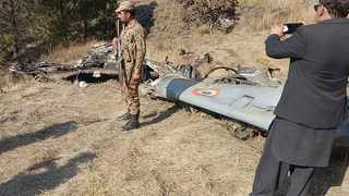 A Pakistani soldier stands guard near the wreckage of an Indian plane shot down by the Pakistan military on Wednesday, in Hurran, near the Line of Control in Pakistani Kashmir. Picture: AP Photo/Abdul Razzaq