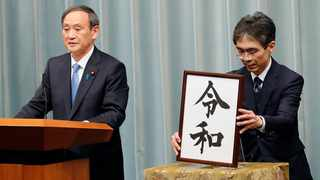 """Japan's Chief Cabinet Secretary Yoshihide Suga, left, speaks after he unveils the name of new era """"Reiwa"""" at the prime minister's office in Tokyo. Picture: AP Photo/Eugene Hoshiko"""