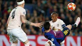 Manchester United captain Ashley Young tries to put pressure on Barcelona opposite number Lionel Messi at the Nou Camp on Tuesday. Photo: Joan Monfort/AP