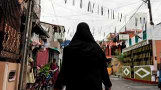 A Muslim woman wearing a hijab walks through a street. An ongoing dispute over the hijab took a violent turn in eastern Malawi leaving three people injured and property damaged. File photo: REUTERS/Danish Siddiqui.