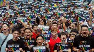 Same-sex marriage supporters gather outside the Legislative Yuan in Taipei, Taiwan. Picture: AP Photo/Chiang Ying-ying