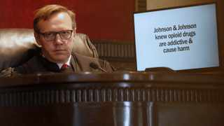Judge Thad Balkman listens during opening arguments for the state of Oklahoma, as the nation's first state trial against drugmakers blamed for contributing to the opioid crisis begins in Oklahoma. At right is a slide from the state's presentation shown on a monitor. Picture: Sue Ogrocki/AP