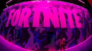 An attendee stops to text next to Epic Games Fortnite sign at E3, the annual video games expo revealing the latest in gaming software and hardware in Los Angeles. Picture: Reuters