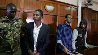 From left to right, defendants Rashid Charles Mberesero, Hassan Aden Hassan and Mohamed Abdi Abikar, are led from the dock by a police officer, left, after their verdict at a court in Nairobi. Picture: Khalil Senosi/AP