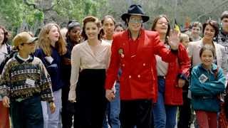 Michael Jackson and Lisa Marie Presley-Jackson welcome children as they arrive for a World Children's Conference at Jackson's Neverland Valley Ranch. Picture: Lee Celano/Reuters