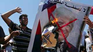 Palestinian demonstrators burn a crossed-out poster depicting U.S. President Trump during a protest against Bahrain's workshop for US Middle East peace plan, in the southern Gaza Strip. Picture: Ibraheem Abu Mustafa/Reuters