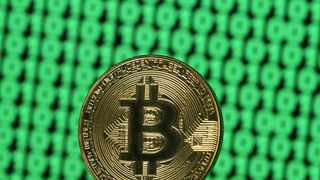 FILE PHOTO: Bitcoin token is seen placed on a monitor that displays binary digits in this illustration picture.