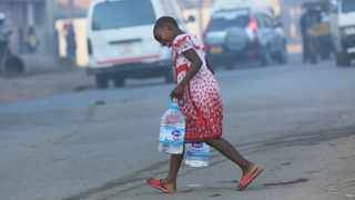 A girl crosses a busy road while carrying water containers in Harare, Friday, 9, 2019.  Fuel prices and the general cost of living continue to rise in Zimbabwe as the public struggle against basic shortages of water and power. (AP Photo/Tsvangirayi Mukwazhi)