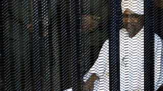 Sudan's former president Omar Hassan al-Bashir sits guarded inside a cage at the courthouse in Khartoum where he is facing corruption charges. Picture: Mohamed Nureldin Abdallah/Reuters
