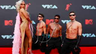 Nikita Dragun and three half-naked guys on the red carpet. Picture: Reuters