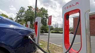FILE - In this July 19, 2019 file photo, a Tesla vehicle charges at a Tesla Supercharger site in Charlotte, N.C. Tesla owners can now buy insurance policies from the electric car company in what may be an essential step toward it selling driverless vehicles. The company says it's now selling policies in California and will go nationwide at an undisclosed date. (AP Photo/Chuck Burton, File)