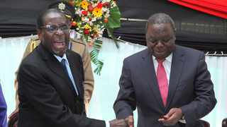 Zimbabwean former president Robert Mugabe, left, shakes hands with Prime Minister Morgan Tsvangirai after he signed the new constitution into law at State house in Harare. Picture: AP Photo/Tsvangirayi Mukwazhi