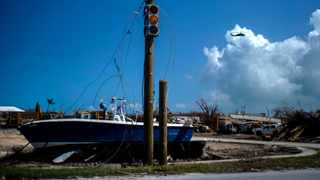 A boat sits on dry land next to a traffic light in the aftermath of Hurricane Dorian, in Abaco, Bahamas. Picture: AP