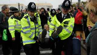 Police officers remove a climate protestor from Lambeth bridge in central London. Picture: Matt Dunham/AP