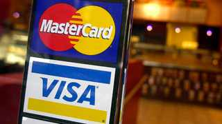"""FILE - This April 22, 2005, file photo, shows logos for MasterCard and Visa credit cards at the entrance of a New York coffee shop. Now, the world's biggest card networks — a group that includes Visa Inc., Mastercard Inc., American Express Co. and Discover Financial Services — have joined forces in an effort to make web purchases easier and reduce what the industry calls """"online cart abandonment."""" ' (AP Photo/Mark Lennihan, File)"""