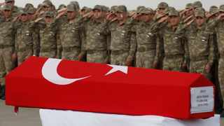 Turkish soldiers salute the Turkish flag-draped coffin of soldier Sefa Findik, killed in action in Syria, during a ceremony at the airport in Sanliurfa, southeastern Turkey. Picture: Lefteris Pitarakis/AP