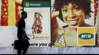 FILE PHOTO: A man walks past an advertising poster for MTN on a street in Lagos, Nigeria