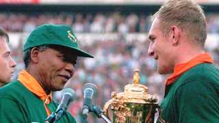 Francios Pienaar receives the Rugby World Cup from former president Nelson Mandela. Picture: Ross Setford/AP