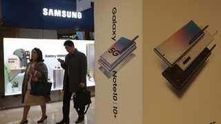 People pass by an advertisement of Samsung Electronics' Galaxy 5G Note10 smartphones at its shop in Seoul, South Korea, Thursday, Oct. 31, 2019. Samsung Electronics said it operating profit for the last quarter fell by nearly 56%, with its robust sales of smartphone, displays and TVs offset by a continuously weak market for computer chips. (AP Photo/Ahn Young-joon)