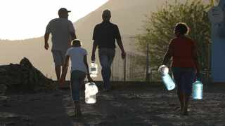 """Township residents carry bottles as they arrive to collect water at a borehole tap set up by the charity """"Gift of the Givers"""" in drought-stricken Graaff-Reinet"""