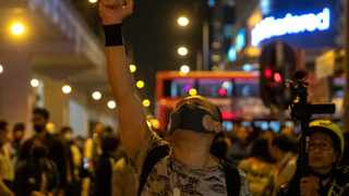 A protester gestures after riot police pull out from a street in Hong Kong. Picture: AP Photo/Ng Han Guan