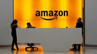 FILE - In this Feb. 14, 2019, file photo people stand in the lobby for Amazon offices in New York. Amazon.com Inc. said it signed up new Prime service members in record numbers in the U.K. last Tuesday and Wednesday.  (AP Photo/Mark Lennihan, File)