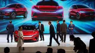 In this April 16, 2019, photo, attendees take a close look at cars from BYD at the Auto Shanghai 2019 show in Shanghai. China's electric car sales are stalling following the end of multibillion-dollar subsidies that made it the biggest market for the technology. Communist leaders want to make China a leader in electric cars but are shifting the burden to the industry by imposing mandatory sales quotas. Photo: AP/Ng Han Guan