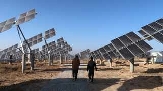Workers walk at a solar power station in Tongchuan, Shaanxi