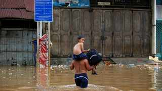 A boy is carried across floodwaters in the Jatinegara area after heavy rains in Jakarta. Picture: Willy Kurniawan/Reuters