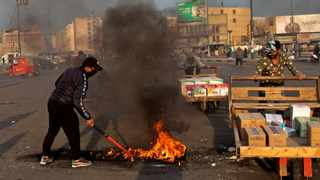 A protester sets fires to close streets near Tahrir Square during a demonstration to protest against the Iranian missile strike, protesters said, in Baghdad, Iraq, Wednesday, Jan. 8, 2020. Iran struck back at the United States early Wednesday for killing a top Revolutionary Guard commander, firing a series of ballistic missiles at two military bases in Iraq that house American troops in a major escalation between the two longtime foes. Photo: Khalid Mohammed/AP