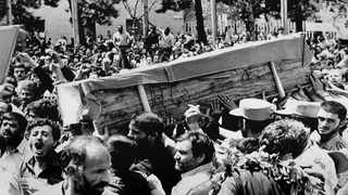 """Iranian mourners carry one of 72 caskets to the Cemetery of Martyrs after attending a """"Death to America"""" rally outside the Majlis, or Iranian parliament, in Tehran, Iran, on July 7, 1988. File picture: Greg English/AP"""