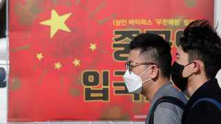 People wearing masks pass by a China's flag with a virus image as South Korean protesters call for a ban on Chinese people entering South Korea. Picture: AP