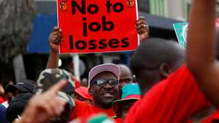 A Cosatu member holds a placard during a march against job losses in Durban. File picture: Reuters