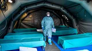 Medical personnel work inside one of the emergency structures that were set up to ease procedures outside the hospital of Brescia, Northern Italy. Picture: Claudio Furlan/LaPresse via AP